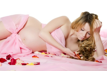 coverlet: The pregnant woman On a pink coverlet Stock Photo
