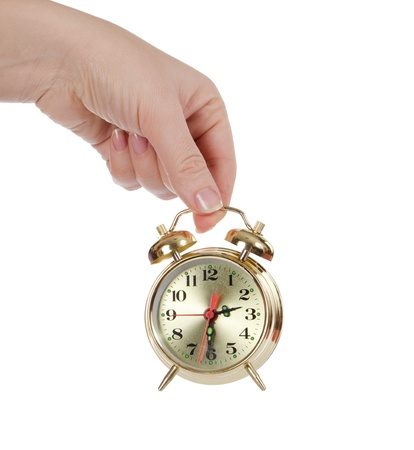 The alarm clock in female hands isolated Stock Photo - 13077563