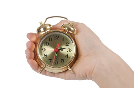 The alarm clock in female hands isolated Stock Photo - 13077493
