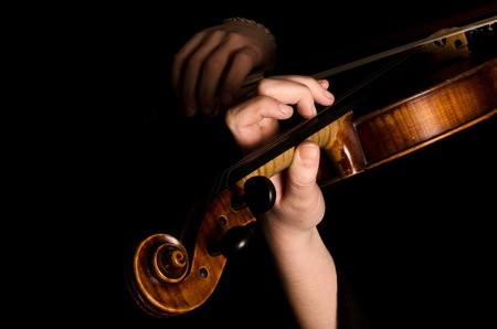 Female hands play a violin on black photo