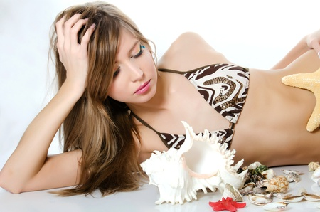 Young girl in bikini lays with seashells Stock Photo - 13287916