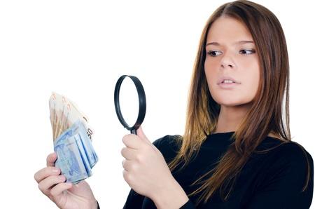 dinero falso: Mujer con lupa y billetes en euros Foto de archivo