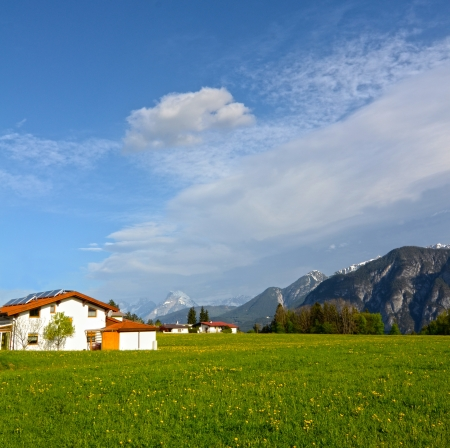 Alpine landscape in Austria: mountains, forests, meadows and a farm