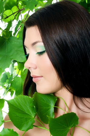 Beautiful woman with spring green leaves. Skincare photo