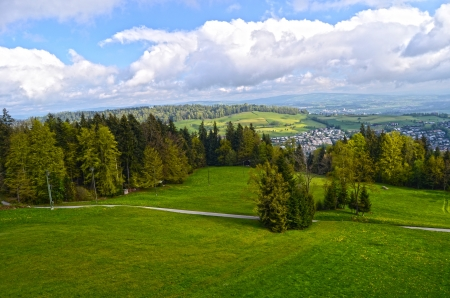 Alpine landscape : mountains, forests, meadows and a farm photo