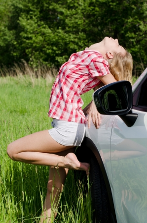 Beautiful girl stands near to white car photo