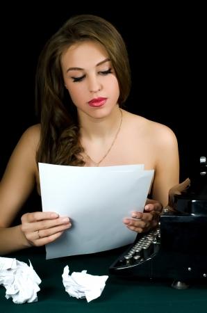 The beautiful girl at a typewriter. Retro photo