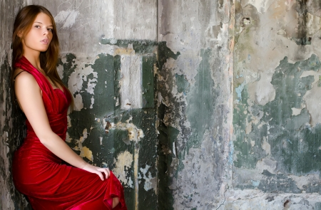 The beautiful girl in an evening dress against an old wall photo