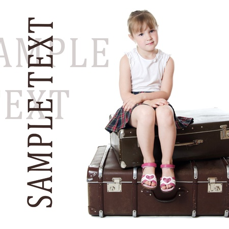 little girl sitting: The little girl on old suitcases isolated