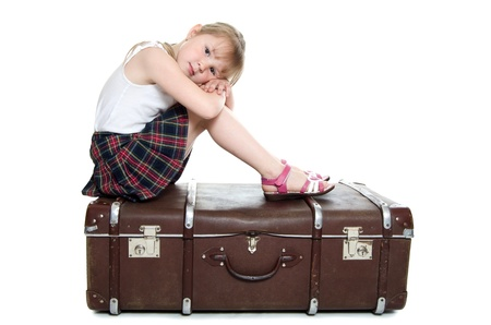 The little girl on old suitcases isolated photo