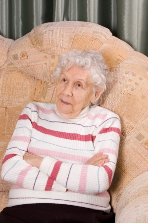 Portrait of the old woman on sofa photo