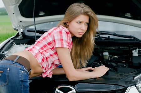 engine bonnet: The beautiful girl repairs the car Stock Photo