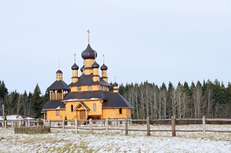 The wooden church against winter wood. Belarus Stock Photo - 14822669