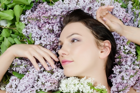 Beautiful woman with flowers of lilac. Skincare photo