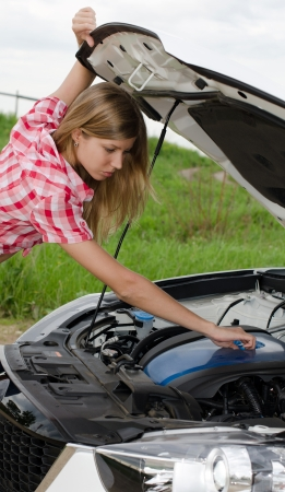 The beautiful girl repairs the car photo