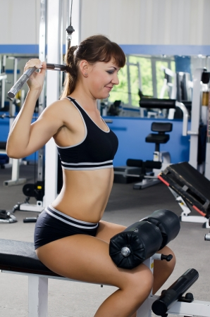 Woman on training apparatus in sports club photo