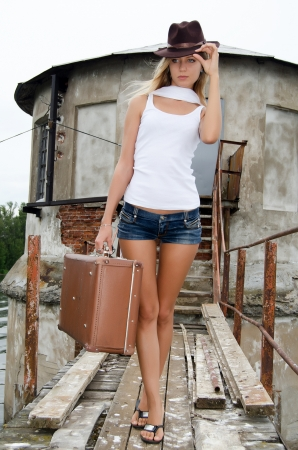 Woman with a suitcase at a pier photo