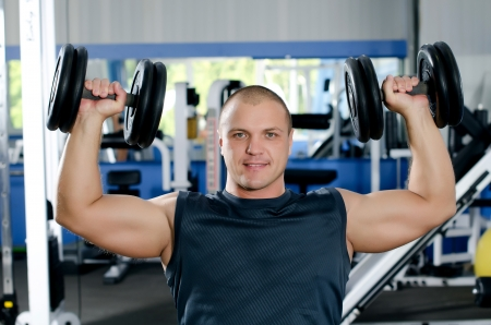 The man with dumbbells in sports club photo