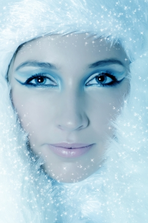 Winter Girl with beautiful make up, silver gloves and snow flake, blue background photo