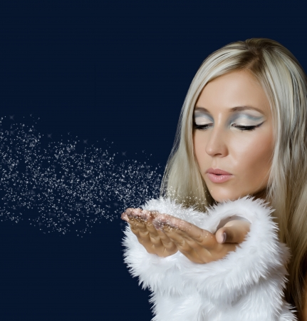 blow kiss: Attracive girl in santa cloth blowing snow from hands