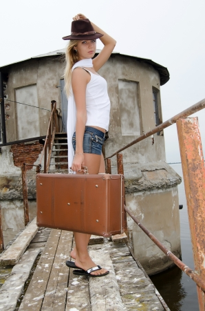 Woman with a suitcase at a pier Stock Photo