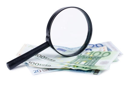The magnifying glass lying on banknotes close-up photo