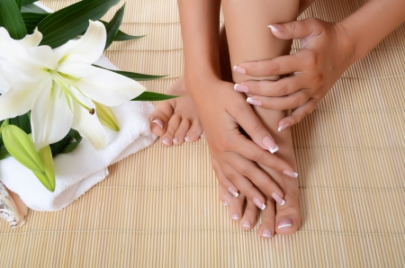 Woman hand and feet with manicure and  Lily photo