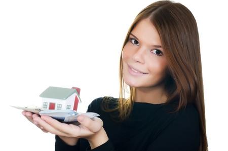 La mujer de negocios con la casa del juguete y billetes