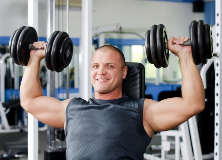 woman lifting weights: The man with dumbbells in sports club Stock Photo