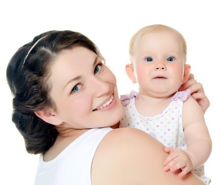 La madre feliz con el bebé sobre blanco