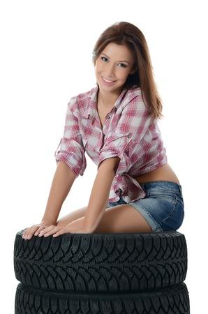 Chica con neumáticos de automóvil aislado en blanco Foto de archivo