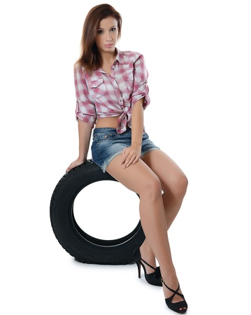 Girl with automobile tyres isolated on white