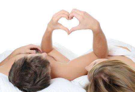 young sex: Красивая пара лежит в постели на белом Фото со стока