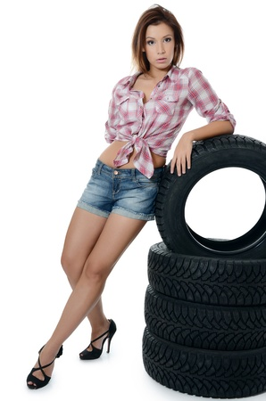Girl with automobile tyres isolated on white photo