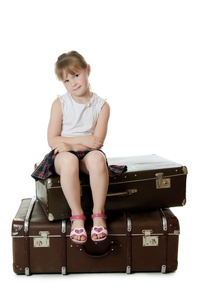 only girls: The little girl on old suitcases isolated
