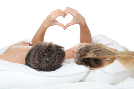 love sex: Beautiful pair lays in bed on white