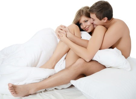 intimate sex: Beautiful pair lays in bed on white