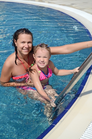 Smiling beautiful woman and her little cute daughter have a fun in pool outdoor photo