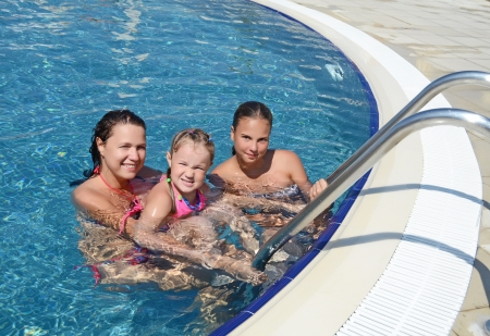 Smiling beautiful woman and her daughter have a fun in pool outdoor photo