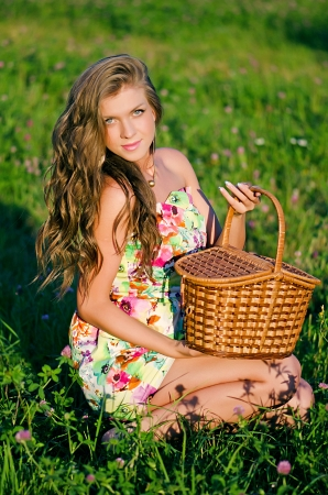 Girl sits in grass with a basket on a sunset photo