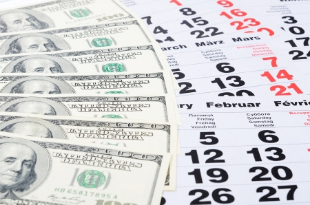 education loan: Banknotes of dollars on calendar sheets close-up Stock Photo