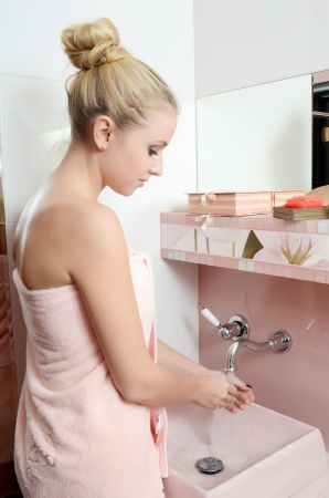 Woman blonde in pink towel washes hands photo