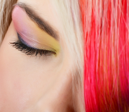 Woman with bright make-up and multi-coloured strand in hair photo