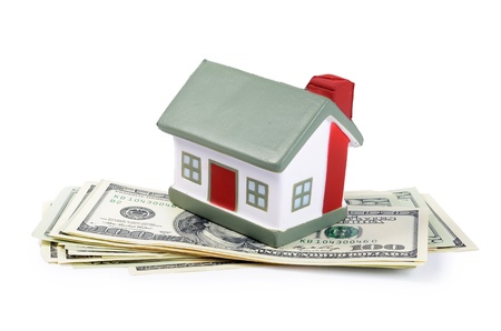 real estate planning: toy house for dollar banknotes as background