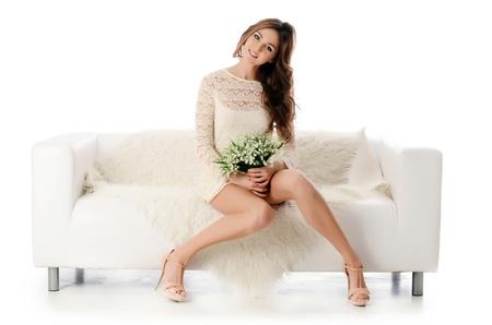 Die schöne Frau. Die Frau in einem weißen Kleid auf einem weißen Sofa. isoliert auf weißem Hintergrund
