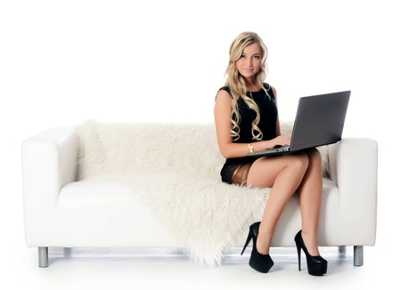 The elegant woman on a white sofa with the laptop. Business concept. photo