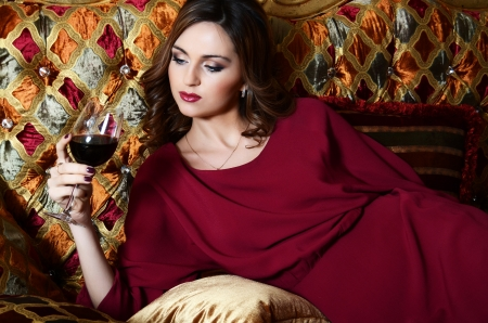 Sensual woman with a red wine glass on a magnificent sofa photo