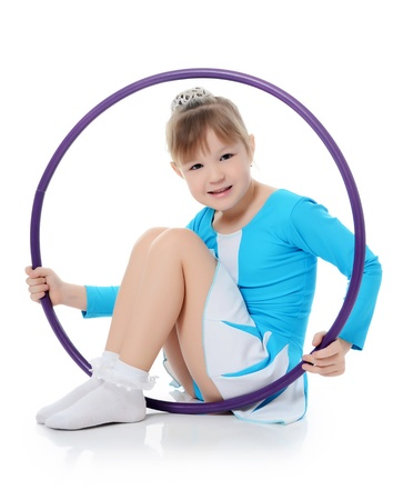 Little girl gymnast does exercise with hoop photo
