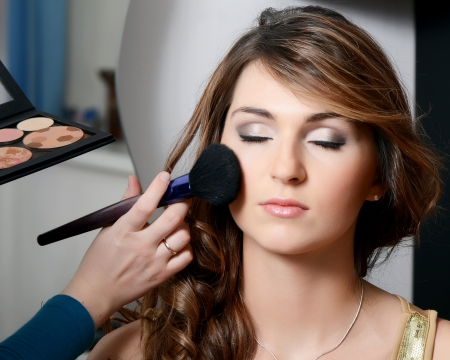 beauty salon face: Beautiful girl put the makeup on the face