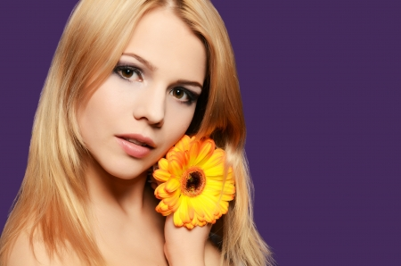 The beautiful woman with a Gerbera flower photo